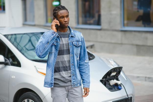 충전 될 그의 전기 자동차를 기다리는 젊은 남자
