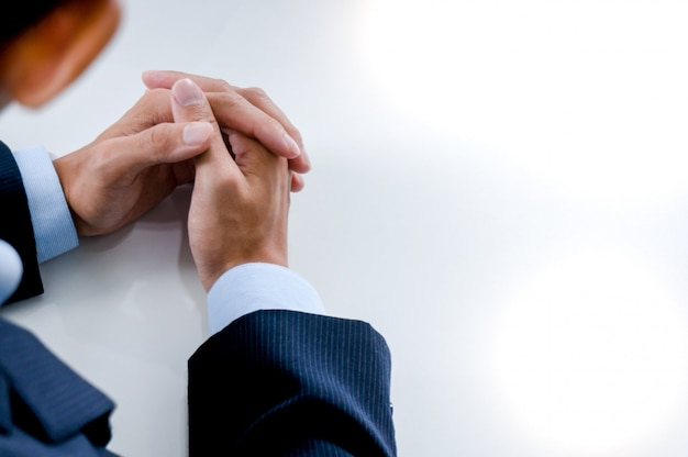 Young man waiting for interview and holding hands folded on a table.