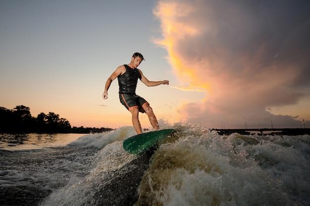 Молодой человек вейксерфинг вниз по реке волны
