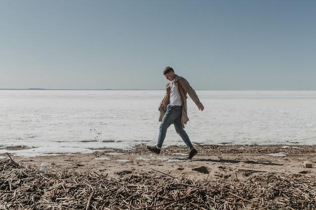 冬のビーチを歩いている若い男。