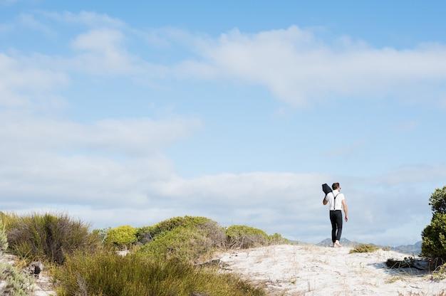 白い砂の上を裸足で歩く若い男