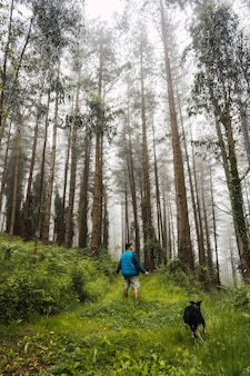 A young man walking in the blue jacket with the dog in the foggy forest