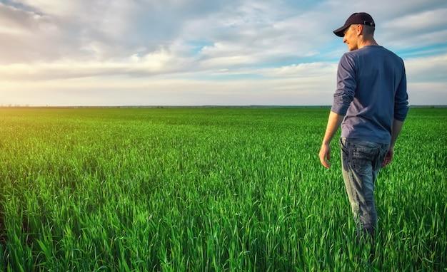 Young man walking in green field. handsome farmer.