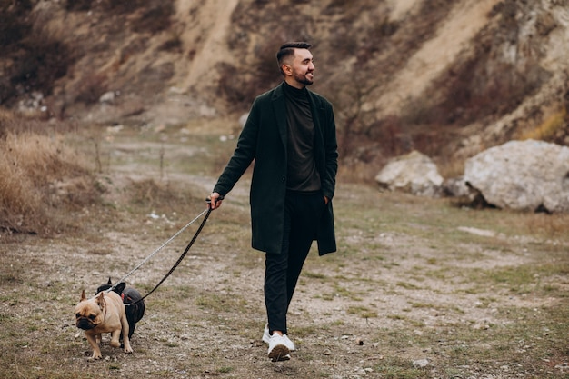 Young man walking his french bulldog in park