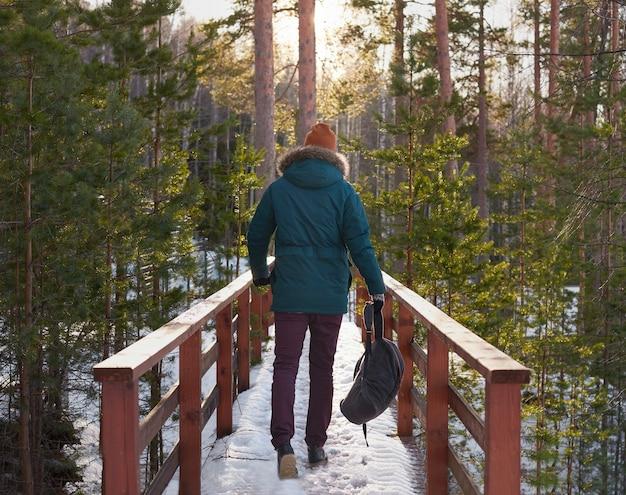 Молодой человек гуляет в лесу
