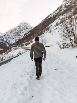 イタリアアルプスの雪山で冬服を着て雪の中を歩く若い男。