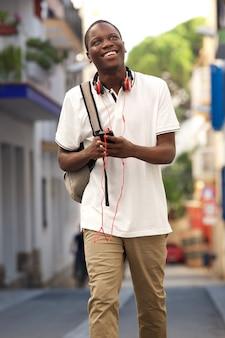 가방과 휴대 전화와 함께 거리에 걷는 젊은 남자