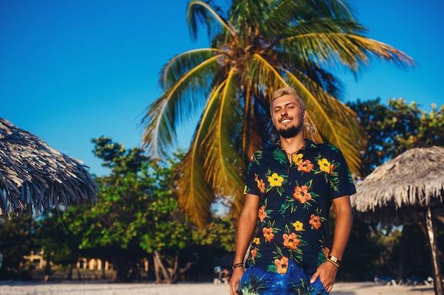 Молодой человек гуляет по пляжу, улыбаясь на фоне пальм