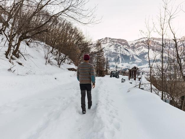 イタリアアルプスの山々で冬服を着て雪の中でオフロード車に向かって歩いている若い男。