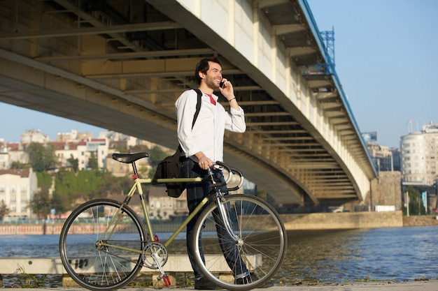 Young man walking with bicycle and talking on mobile phone