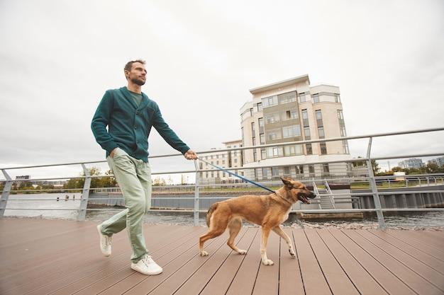 도시 거리를 따라 가죽 끈에 독일 셰퍼드와 함께 걷는 젊은 남자
