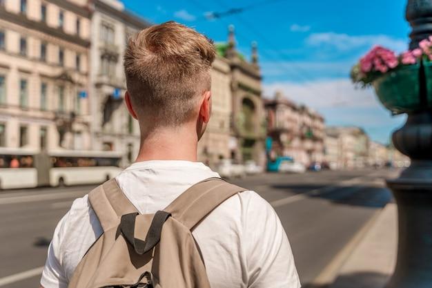 Молодой человек гуляет по центру петербурга летом