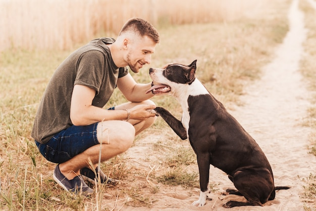 A young man walks in nature with a dog of the pit bull terrier breed