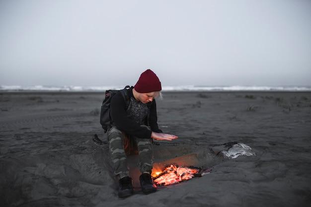 火のそばで暖まる若い男