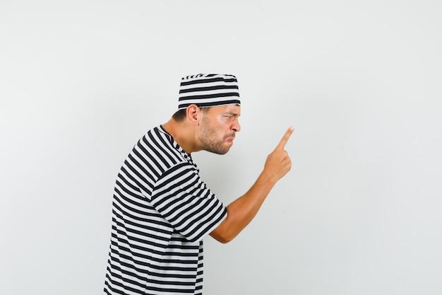 스트라이프 티셔츠, 모자에 손가락으로 경고하고 화가 찾고 젊은 남자.