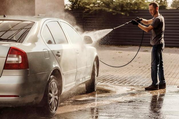 Молодой человек моет машину на автомойке самообслуживания