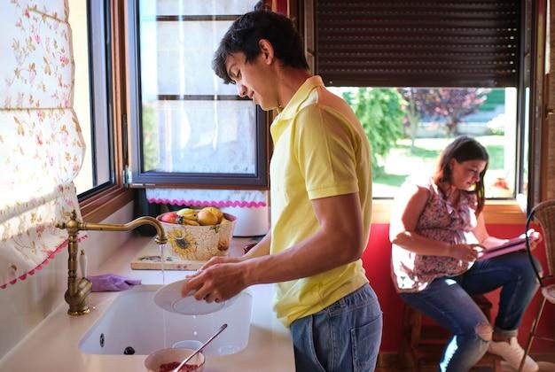 그의 아내가 태블릿을 사용하는 동안 젊은 남자는 부엌에서 설거지