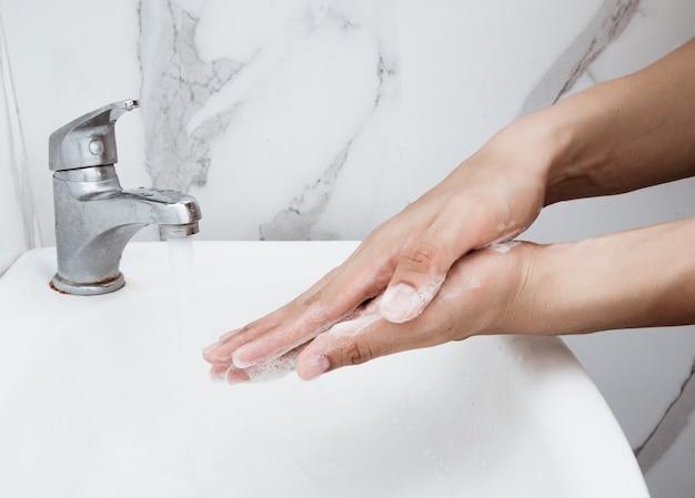 若い男がバスルームのシンク、クローズアップ、コロナウイルスまたはcovid-19予防で手を洗って、衛生を停止します。