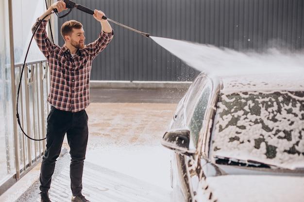 Молодой человек моет машину на автомойке
