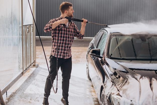 洗車場で車を洗う若い男