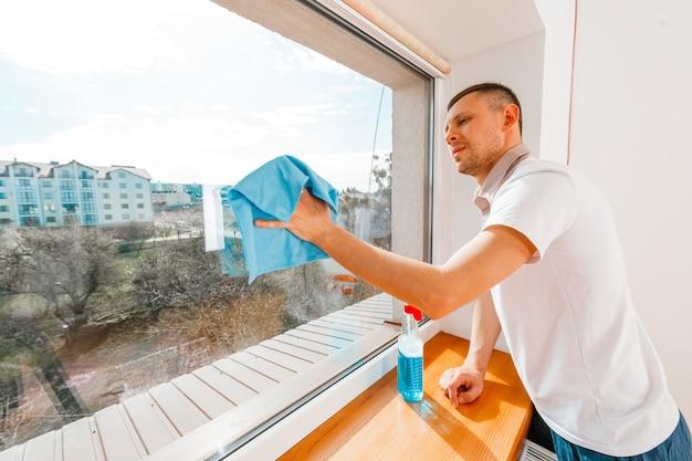 若い男がオフィスで窓を洗う