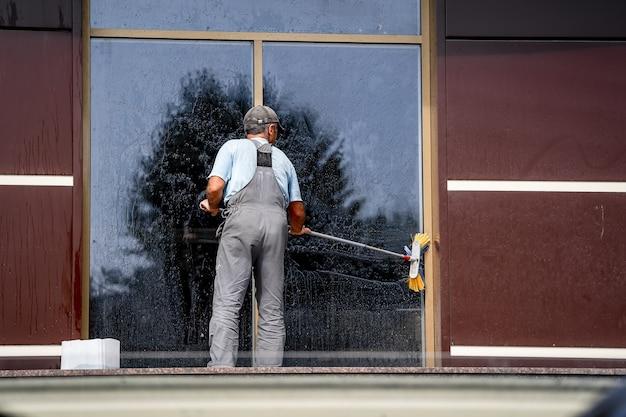 젊은 남자 세척 창 야외. 전문 청소. 큰 파노라마 창.