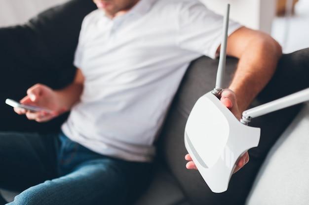 Молодой человек смотрит телевизор в собственной квартире. отрежьте взгляд парня держа роутер wi0fi в руке. настраивая это. попробуйте позвонить с помощью мобильного телефона или смартфона. устройство нуждается в ремонте.