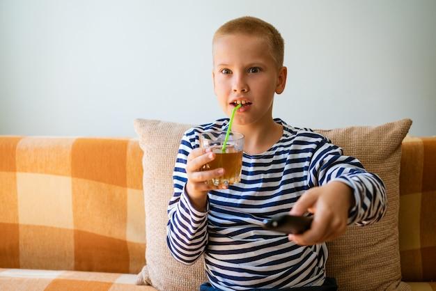 젊은 남자는 채널을 변경하기 위해 리모콘을 사용하여 tv를 봅니다. 남자는 tv에서 보는 것이 지루해졌습니다...