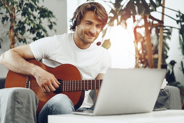 Young man watching guitar tutorial on his laptop at home