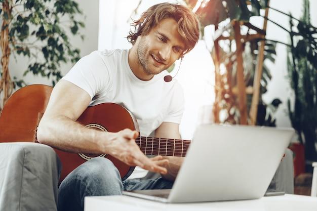 若い男が彼のラップトップでギターのチュートリアルを見て