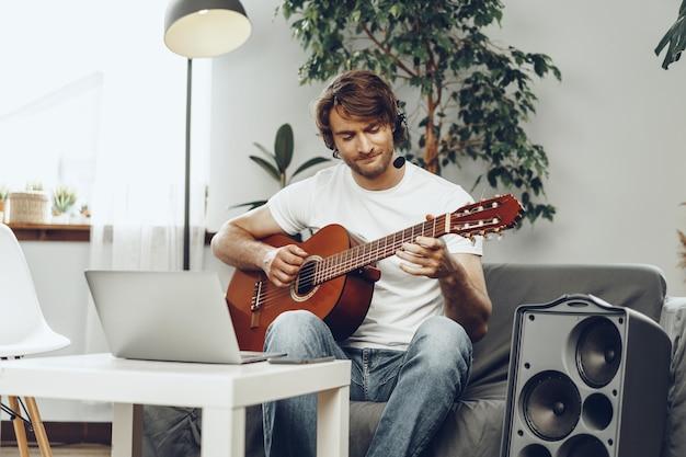 Молодой человек смотрит учебник по игре на гитаре на своем ноутбуке