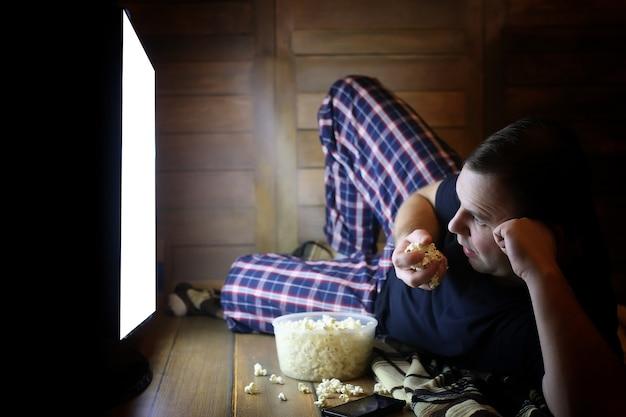 床で家でテレビを見て、ポップコーンを食べる若い男