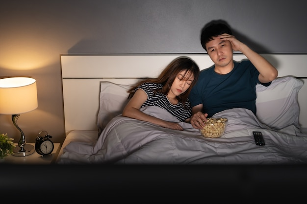 Молодой человек смотрит телевизор в своей постели со своей женой. сонное и усталое выражение лица страдает бессонницей