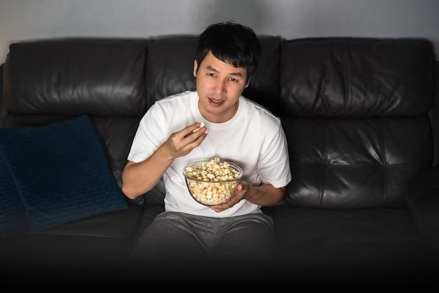 Молодой человек смотрит телевизор и ест попкорн на диване ночью