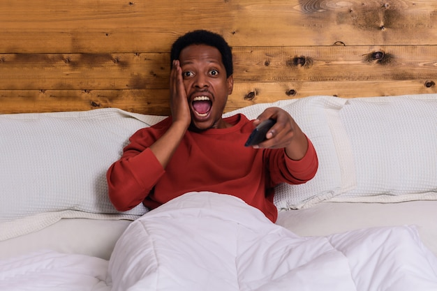 Young man watching tv on bed at home.