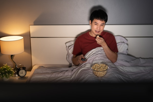 Young man watching tv and eating popcorn on a bed at night
