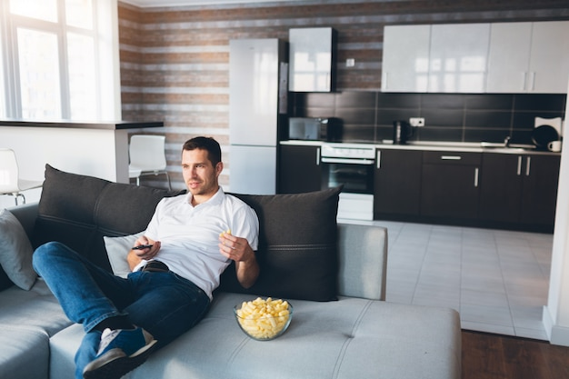 Young man watching tv in his own apartment. sit alone on couch and eat snacks. use remote control for switching tv channels.