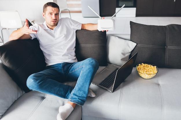 Молодой человек смотрит телевизор в собственной квартире. смущенный отвлеченный парень держит в руке wi-fi роутер и не знает, как заставить его работать или настраивать его.