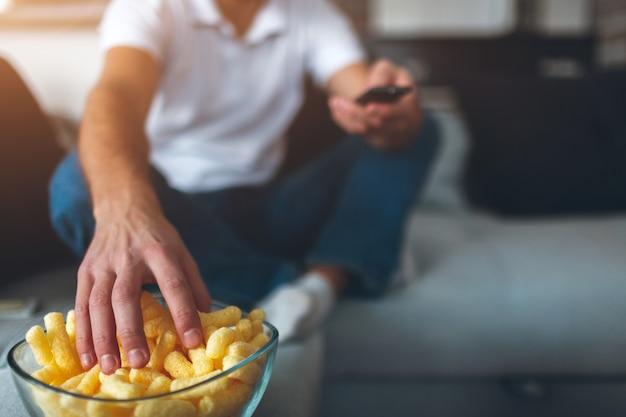 若い男が自分のアパートでテレビを見ています。映画を見るために不健康だがおいしいスナックでボウルに手を伸ばす男のビューをカットします。