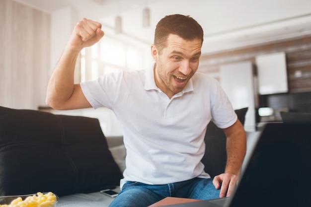 자신의 아파트에서 tv를 시청하는 젊은 남자. 영화 나 스포츠 게임을 보는 동안 환호하는 감정적 인 행복한 사람.