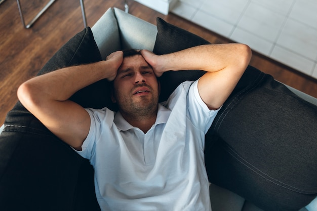 Молодой человек смотрит телевизор в собственной квартире. головная боль, боль или похмелье. держаться за голову и страдания.