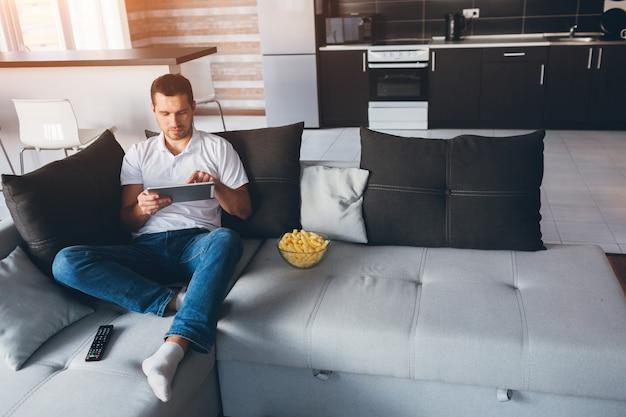 자신의 아파트에서 tv를 시청하는 젊은 남자. 소파에 앉아서 태블릿으로 작업하십시오. 터치 스크린. 집에서 원격 작업. 방에 집중된 근면 한 사람. 일광.