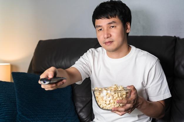 Молодой человек смотрит телевизор на диване ночью