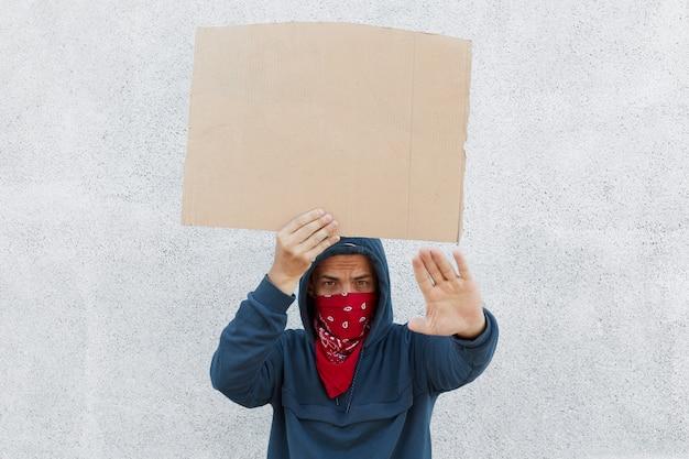 Il giovane ondeggia il cartello fatto a mano del cartone con spazio per l'iscrizione