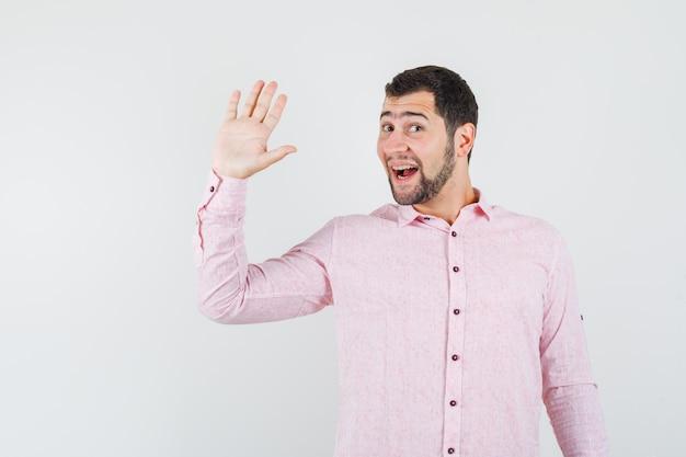 ピンクのシャツで挨拶と陽気に手を振って若い男