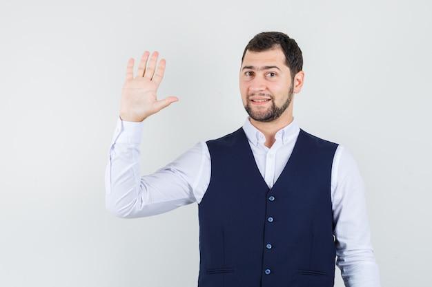 シャツとベストで挨拶のために手を振って、陽気に見える若い男