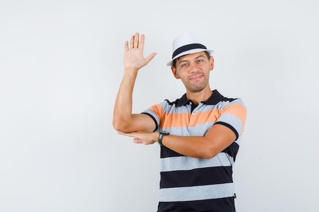 Tシャツと帽子で挨拶と陽気に手を振って若い男