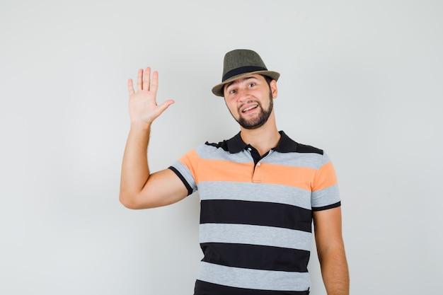 Tシャツ、帽子、陽気に挨拶するために手を振る若い男。
