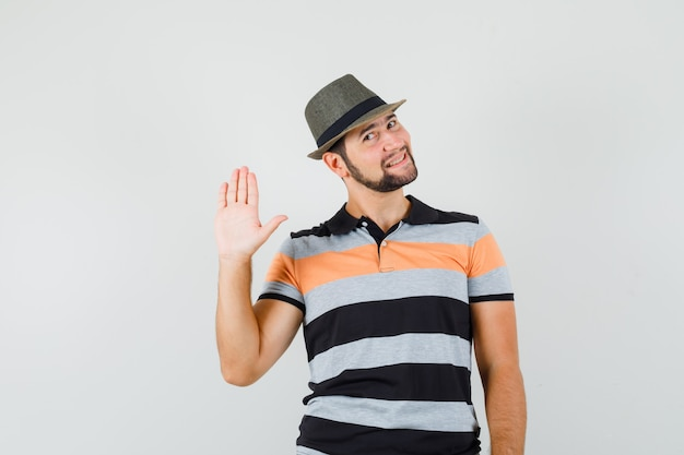 Tシャツ、帽子、陽気に挨拶するために手を振る若い男
