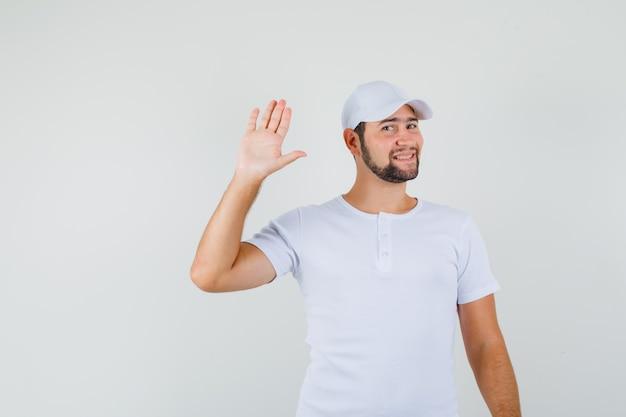 白いtシャツ、キャップ、新鮮な外観、正面図で挨拶のために手を振っている若い男。